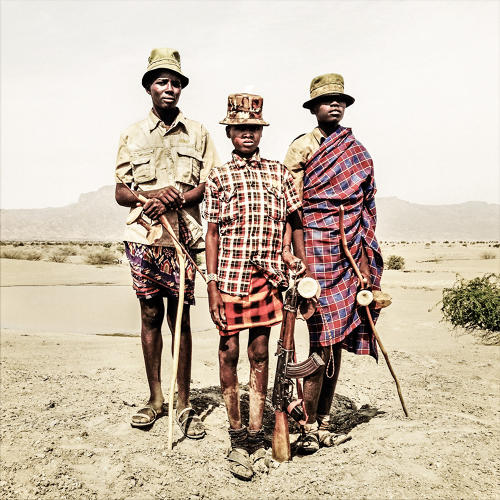 <p>Ebei Edapal, Esekon Eipan, and Ebulon Louyongorot stand on the Todonyang plains near a watering hole in Kenya on February 11, 2014.</p>  <p>The teenage boys started carrying guns as early as seven years old to protect their herd from the frequent attacks of the rival Daasanach tribe.</p>  <p>With the changing climate the Turkana herdsmen, who traditionally practice a nomadic pastoralist lifestyle in the arid northwestern tip of Kenya, struggle to cope with the harsh consequences of the prolonged drought. Across the border in Ethiopia the Daasanach are pushing into Turkana territory as their government handed most of their traditional lands over to large-scale farming developers. Competing for the fishing grounds of Lake Turkana and the pastures around it, the rival communities are trapped in a vicious cycle of conflict as they struggle to survive.</p>