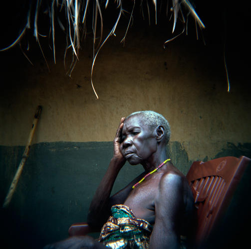 <p>An elderly woman suffering from chronic intestinal illnesses sits in front of her home in South Sudan. Due to decades of conflict and unexploded ordinance left over from the war, her village, near the town of Yei, has no potable water or public services. Villagers take water directly from the river for drinking, washing, and cooking. In addition to living with the consequences of conflict, communities in the Horn of Africa must contend with the affects of climate change. According to the World Health Organization, &quot;climate change is expected to affect the capacity of existing water and sanitation infrastructure and services. These services have to prepare for the widely anticipated consequences of floods and droughts, or risk compromising access to drinking water and adequate sanitation for substantial numbers of people in developing and developed countries, with cascading effects on human health and development.&quot;<br /> Yei, South Sudan. 27/06/2011.</p>