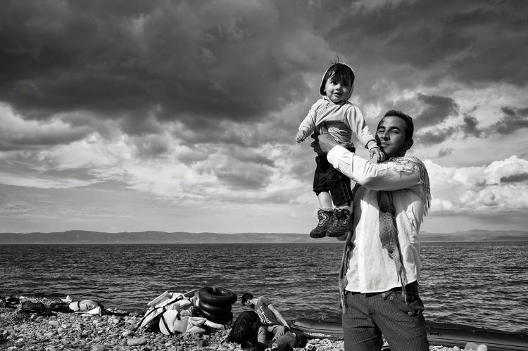 <p>Lesbos, Greece, 2015: A father celebrates his family's safe passage to Lesbos after a stormy crossing over the Aegean Sea from Turkey. ©Tom Stoddart</p>