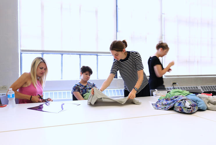 <p>Team Eliza putting the final touches on their design. Eleven-year-old Eliza (center) has autism, which causes her to tear or pick at her clothes.</p>