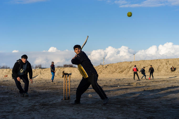 <p>Outside the entrance of the Jungle, youngsters play cricket in the open space next to the highway that leads to the Calais port.</p>