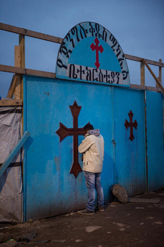 <p>A man praying early in the morning at the entrance of the Eritrean church.</p>