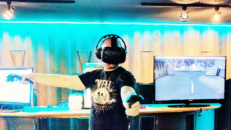 <p>A player faces off against zombies invading his office building in a virtual reality game.</p>