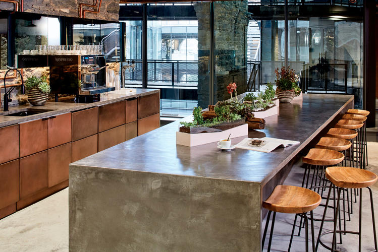 <p>The communal kitchen features natural stone finishes, copper cabinet fronts, and industrial-inspired furniture.</p>