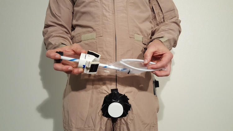 <p>Thatcher Cardon, a family physician and in-flight surgeon for the U.S. Air Force, demonstrates his solution to NASA's Space Poop Competition.</p>